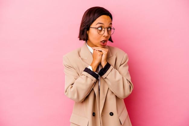Jonge bedrijfs gemengde rasvrouw die op roze muur wordt geïsoleerd die voor geluk bidt, verbaasd en mond opent die naar voorzijde kijkt.