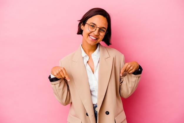 Jonge bedrijfs gemengde rasvrouw die op roze muur wordt geïsoleerdm naar beneden wijst met vingers, positief gevoel