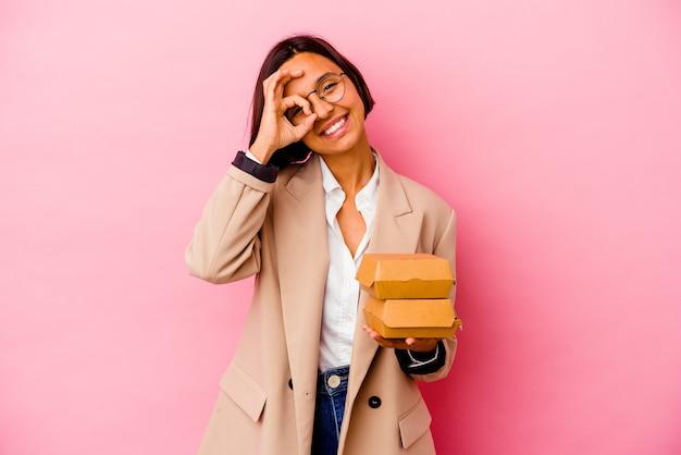 Jonge bedrijfs gemengde rasvrouw die op roze opgewekte muur wordt geïsoleerd die ok gebaar op oog houdt