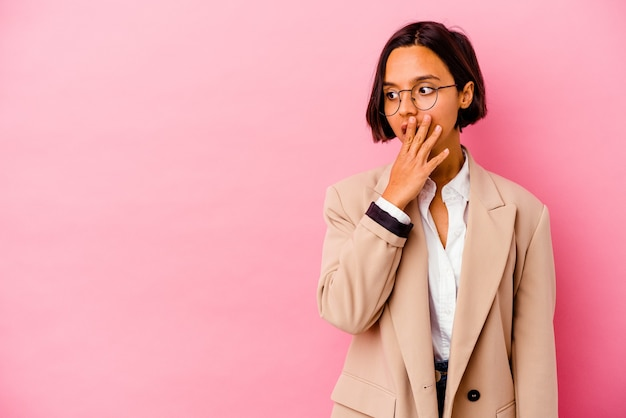 Jonge bedrijfs gemengde rasvrouw op roze nadenkend op zoek naar een exemplaarruimte die mond behandelt met hand.