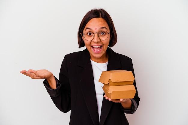 Jonge bedrijfs indische vrouw die geïsoleerde hamburgers eet die een aangename verrassing ontvangen, opgewekt en handen opheft.