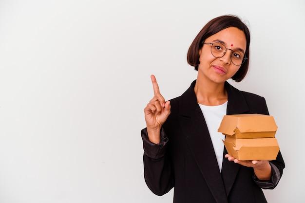 Jonge bedrijfs indische vrouw die geïsoleerde hamburgers eet tonend nummer één met vinger.