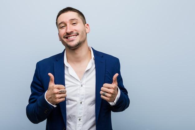 Jonge bedrijfs kaukasische man die beide duimen opheft, glimlachend en zeker.