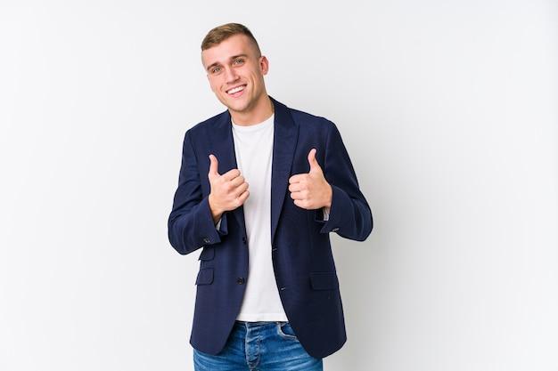 Jonge bedrijfs kaukasische mens die beide duimen omhoog opheft, glimlachend en zeker.