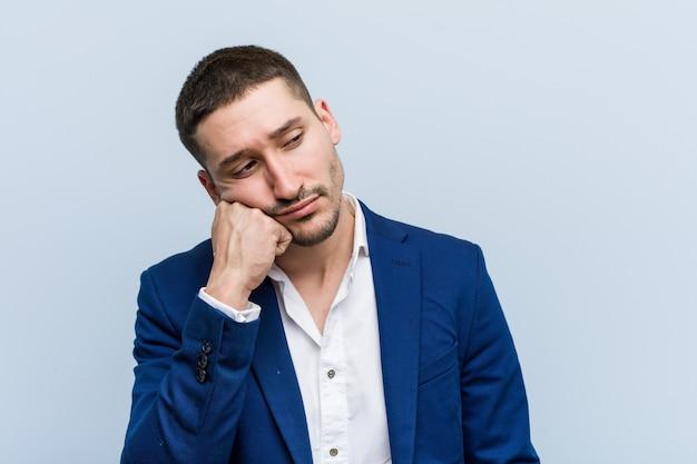 Jonge bedrijfs kaukasische mens die droevig en peinzend voelt, die copyspace kijken.