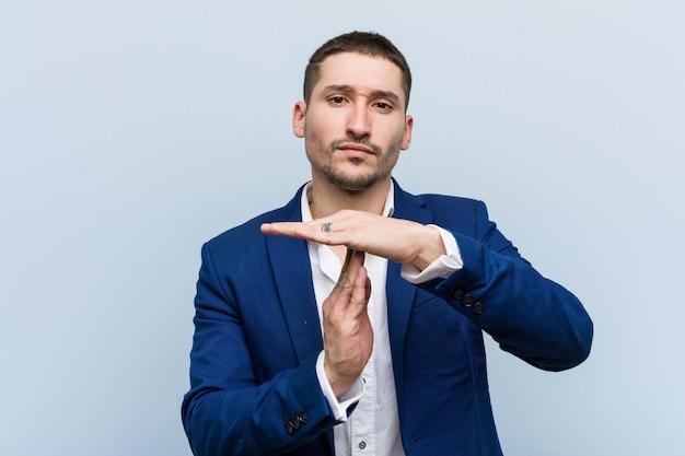 Jonge bedrijfs kaukasische mens die een time-outgebaar toont.