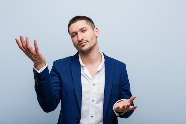 Jonge bedrijfs kaukasische mens die tussen twee opties twijfelt.