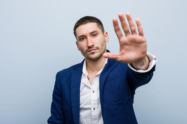 Jonge bedrijfs kaukasische mens die zich met uitgestrekte hand bevindt die stopteken toont, dat u verhindert.
