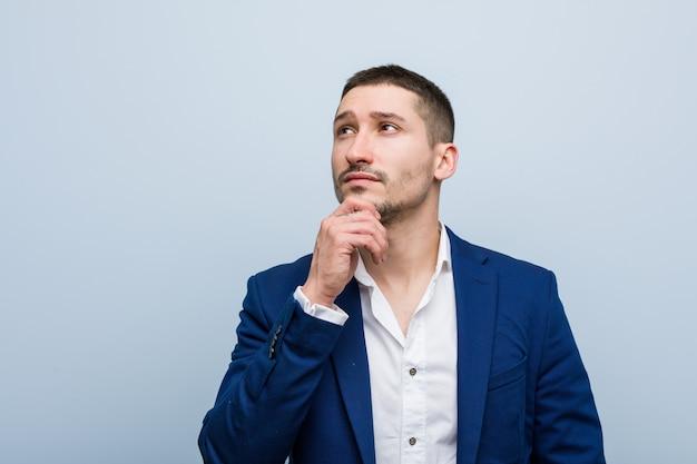Jonge bedrijfs kaukasische mens die zijdelings met twijfelachtige en sceptische uitdrukking kijkt.