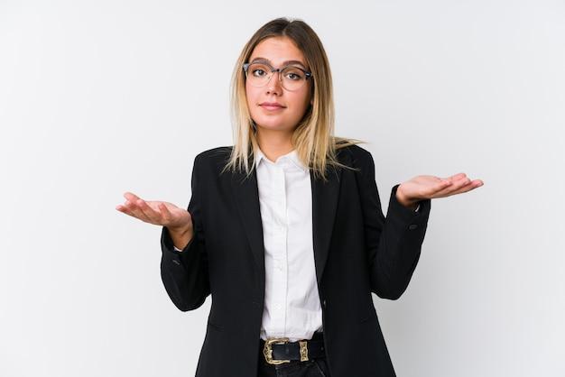 Jonge bedrijfs kaukasische vrouw die en schouders in het vragen van gebaar twijfelen ophalen.