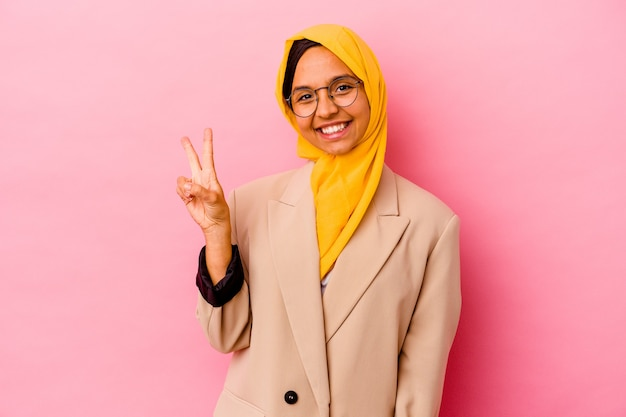 Jonge bedrijfs moslimvrouw die op roze muur wordt geïsoleerd die overwinningsteken toont en breed glimlacht