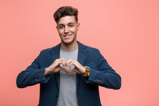 Jonge bedrijfs natuurlijke mens die en een hartvorm met hem glimlacht toont handen.