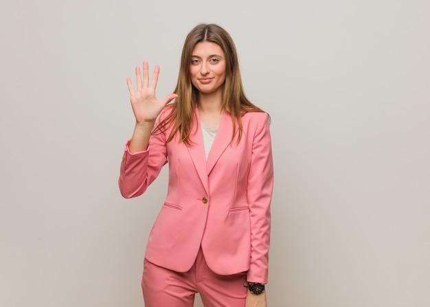 Jonge bedrijfs russische vrouw die nummer vijf toont