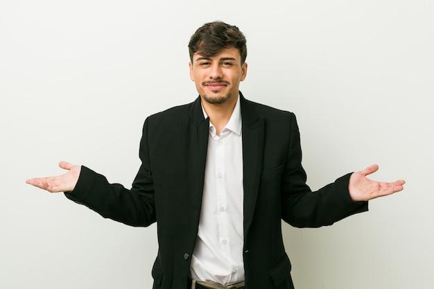 Jonge bedrijfs spaanse mens die en schouders in twijfel vragen gebaar opheffen.