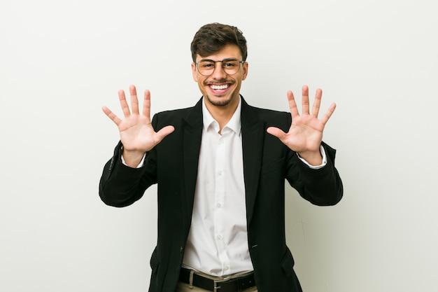 Jonge bedrijfs spaanse mens die nummer tien met handen toont.