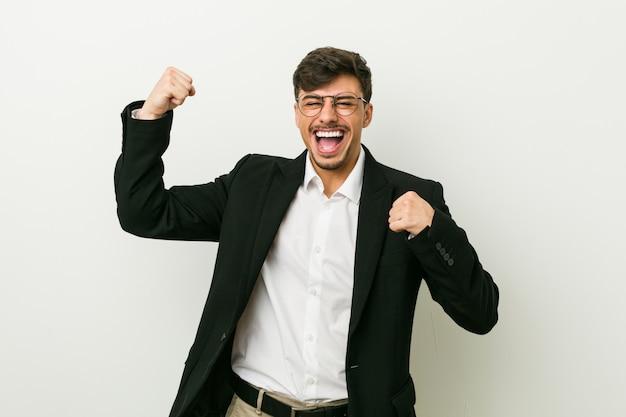 Jonge bedrijfs spaanse mens die vuist na een overwinning, winnaar opheft.