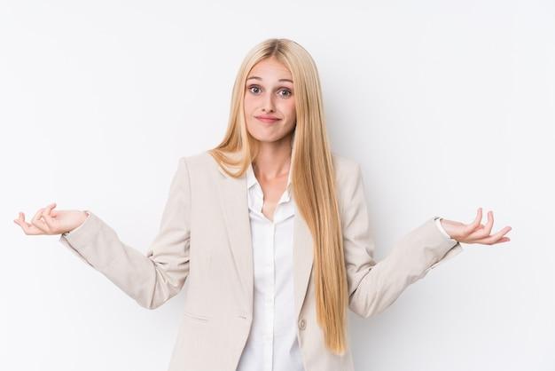 Jonge bedrijfsblonde vrouw op witte muur die en schouders in het vragen van gebaar twijfelen ophalen.