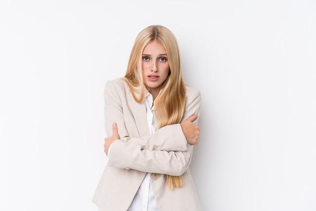 Jonge bedrijfsblonde vrouw op witte muur die koud wegens lage temperatuur of een ziekte gaat.
