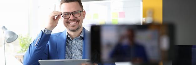 Jonge bedrijfscoach die lacht en een bril aanpast bij online bedrijf voor mobiele telefoons