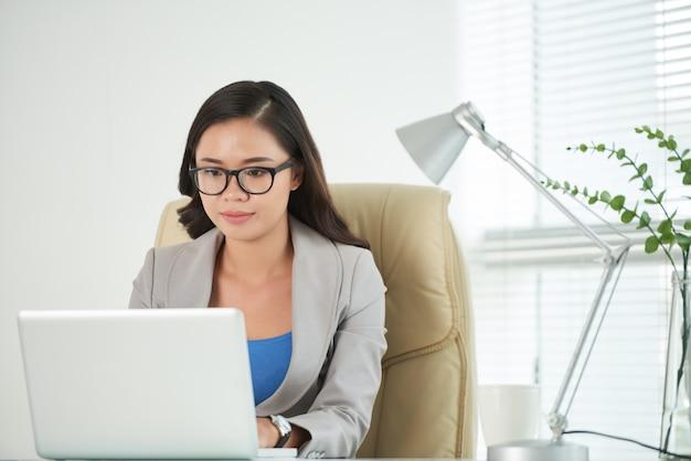 Jonge bedrijfsdame die document op laptop in het bureau opstellen