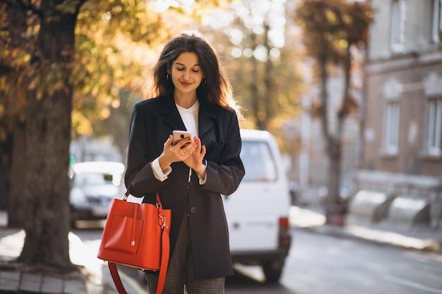 Jonge bedrijfsdame die telefoon in de straat met behulp van