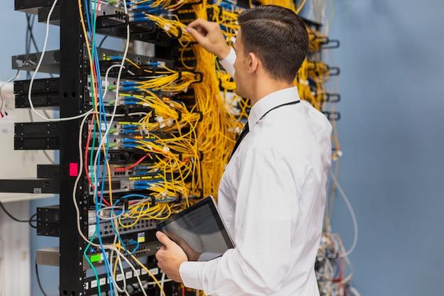 Jonge bedrijfsingenieur die in een ruimte van de netwerkserver werkt