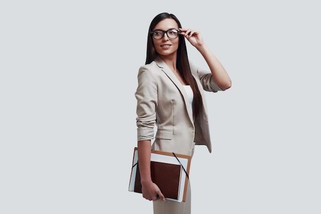 Jonge bedrijfskundige. aantrekkelijke jonge vrouw die brillen aanpast terwijl ze tegen een grijze achtergrond staat