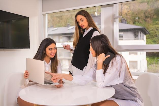 Jonge bedrijfsmeisjes in informele ontmoeting met computer in witte overhemden.