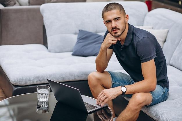 Jonge bedrijfsmens die aan een computer thuis werkt
