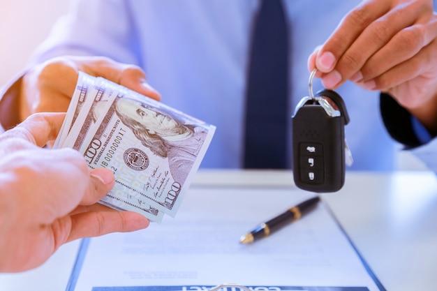 Jonge bedrijfsmens die auto met sleutels van klant geeft.