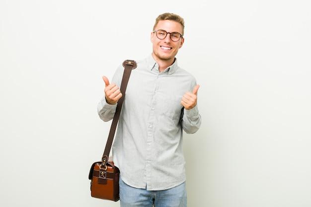 Jonge bedrijfsmens die beide duimen omhoog opheft, glimlachend en zeker