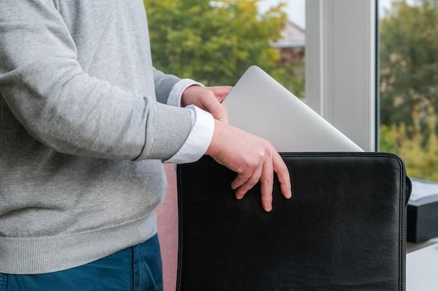 Jonge bedrijfsmens die een laptop uit een leergeval op kantoor trekt.