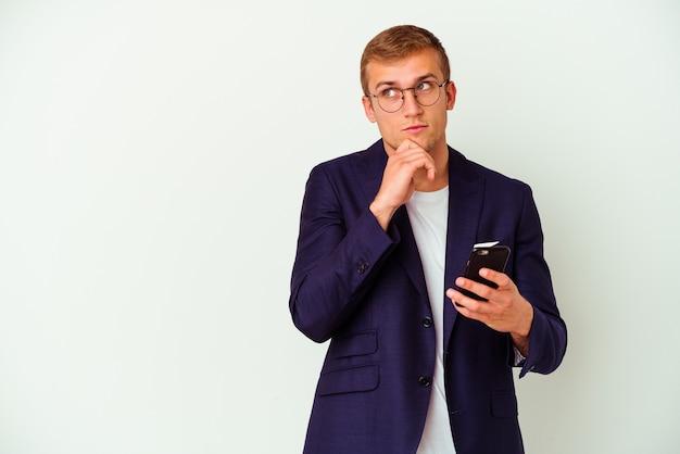 Jonge bedrijfsmens die een mobiele telefoon houdt die op witte muur wordt geïsoleerd die zijwaarts met twijfelachtige en sceptische uitdrukking kijkt.