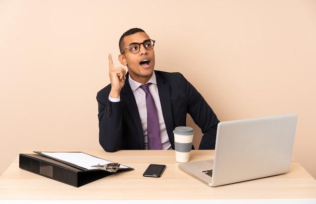 Jonge bedrijfsmens die in zijn bureau met laptop en andere documenten een idee denkt dat de vinger benadrukt
