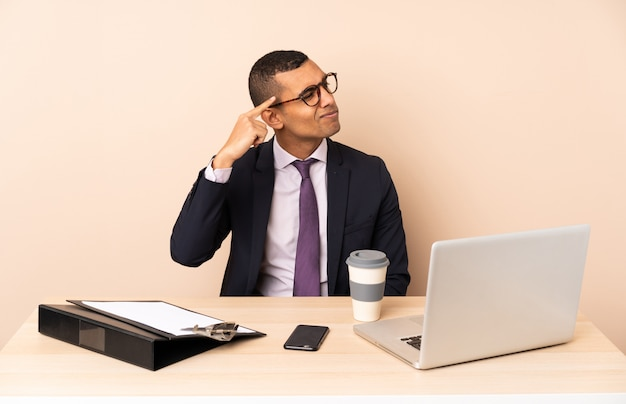 Jonge bedrijfsmens die in zijn bureau met laptop en andere documenten het gebaar van waanzin maakt die vinger op het hoofd zet
