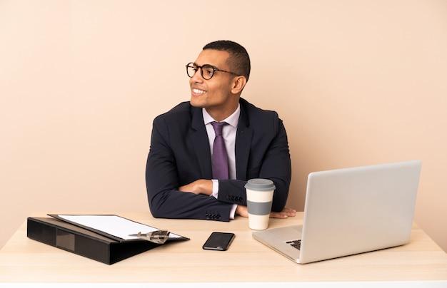 Jonge bedrijfsmens die in zijn bureau met laptop en andere documenten kant kijkt
