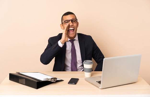 Jonge bedrijfsmens die in zijn bureau met laptop en andere documenten met wijd open mond schreeuwt