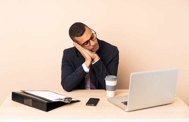 Jonge bedrijfsmens die in zijn bureau met laptop en andere documenten slaapgebaar in aanbiddelijke uitdrukking maakt