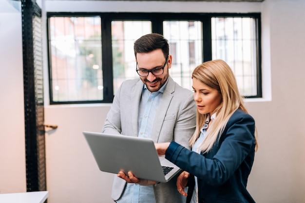 Jonge bedrijfsmens die laptop houdt terwijl het bespreken van nieuw project met zijn vrouwelijke collega