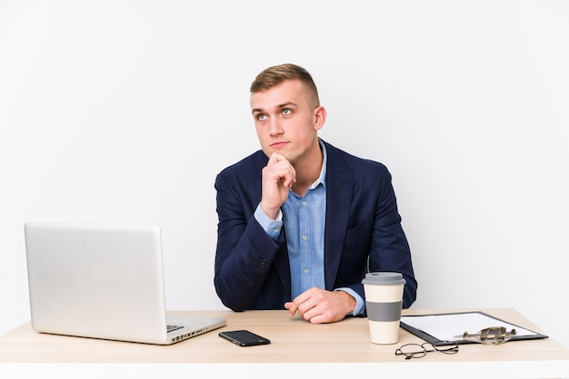 Jonge bedrijfsmens die met laptop zijwaarts kijkt met twijfelachtige en sceptische uitdrukking.