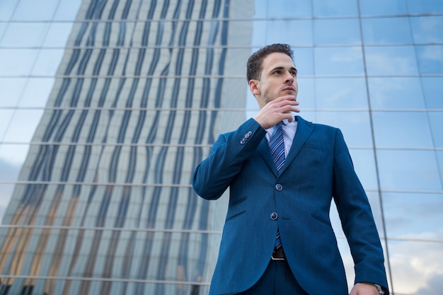 Jonge bedrijfsmens die naar de toekomst kijkt die een gebaar van succes maakt.