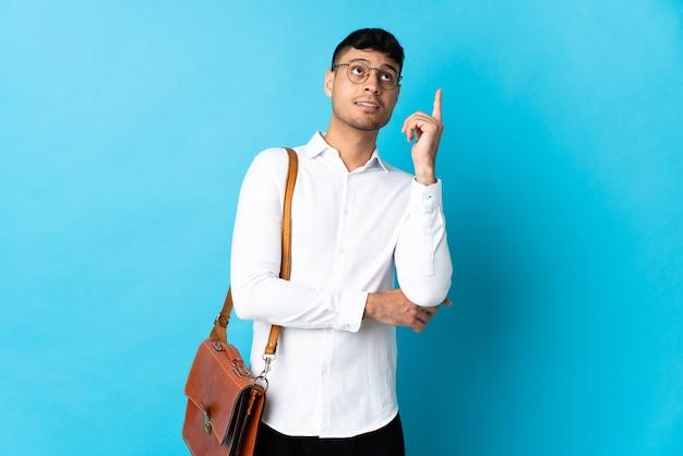 Jonge bedrijfsmens die op blauw wordt geïsoleerd dat een geweldig idee benadrukt