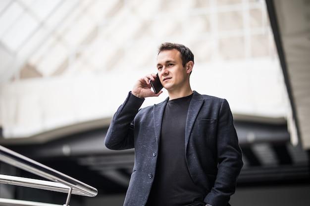 Jonge bedrijfsmens die op celtelefoon spreken op modern kantoor