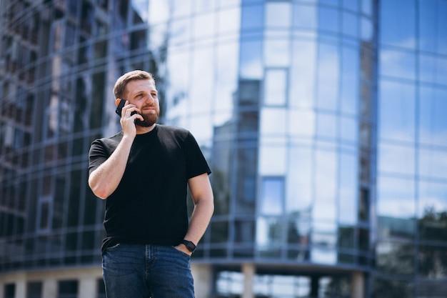 Jonge bedrijfsmens die op telefoon door de wolkenkrabber spreekt