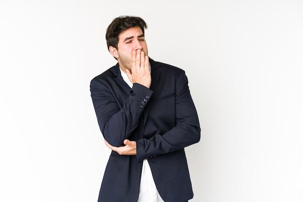 Jonge bedrijfsmens die op witte achtergrond wordt geïsoleerd die geeuwt die een moe gebaar toont dat mond behandelt met hand.