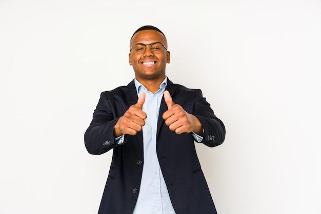 Jonge bedrijfsmens die op witte muur met duimen ups wordt geïsoleerd, juicht over iets toe