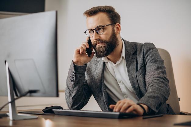 Jonge bedrijfsmens die over telefoon spreekt en aan computer werkt