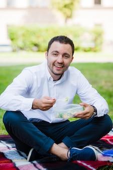 Jonge bedrijfsmens die van voedsel geniet dat hij in een lunchdoos van huis bracht. lunch in het park buiten.