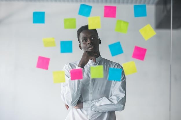 Jonge bedrijfsmens die zich voor de muur van het stickersglas bevinden en op toekomstplannen op zijn kantoorplaats kijken