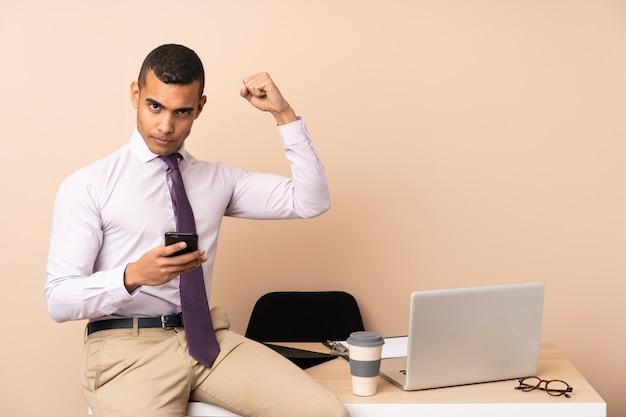 Jonge bedrijfsmens in een bureau dat een overwinning viert